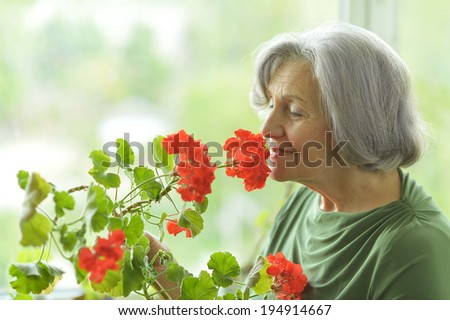 Senior woman with red flowers at home - stock photo