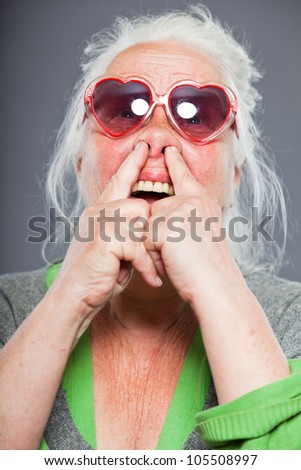 Senior woman with sunglasses making funny faces. Expressive. Studio shot isolated on grey background. - stock photo