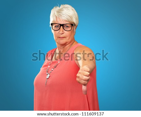 Senior Woman With Thumbs Down Isolated On Blue Background - stock photo