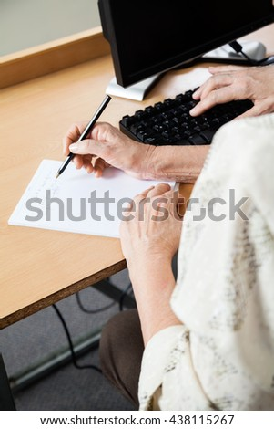 Senior Woman Writing Notes In Computer Class - stock photo