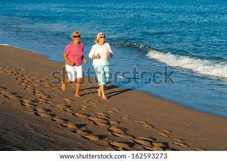 Senior women having early morning jog along sandy beach. - stock photo