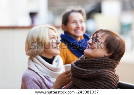 Senior women in warm clothes having cup of hot tea on terrace - stock photo
