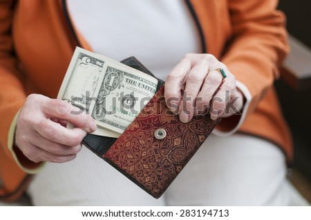 Senior women looks in her purse with US dollar bills. - stock photo
