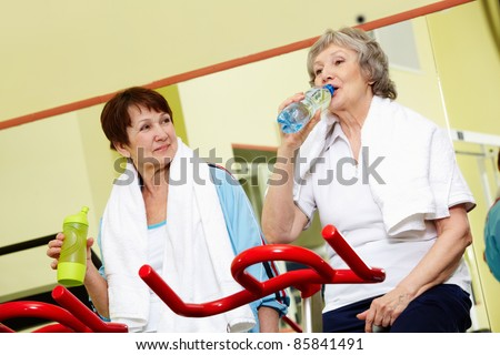 Senior women taking a drink in gym - stock photo