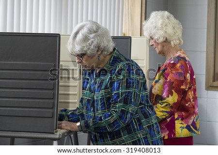 Senior women voting in a voting booth - stock photo