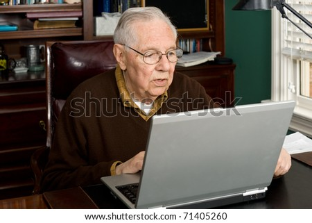 Senior working on a laptop - stock photo
