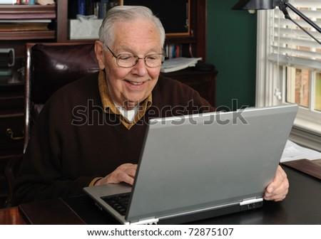 Senior working on a laptop - stock photo