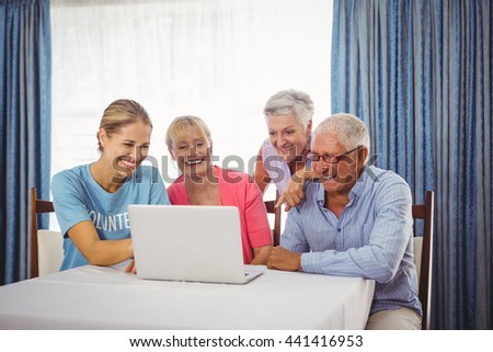 Seniors and woman using laptop in retirement house - stock photo