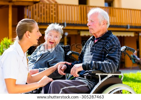 Seniors, couple of man and woman sitting in wheelchair, nurse holding hands with them - stock photo