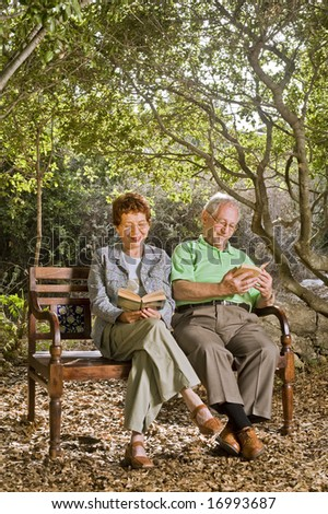 seniors couple sitting on a bench reading books in the park - stock photo
