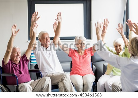 Seniors doing some exercises in a retirement home - stock photo