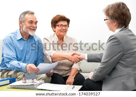 Seniors ouple meeting with financial adviser, handshake - stock photo