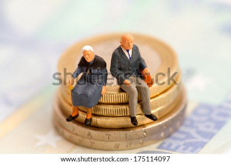Seniors sitting on stack of coins - stock photo