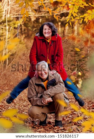 seniors walking in autumn forest / jumping - stock photo
