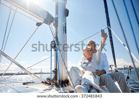 seniors with smartphone taking selfie on yacht - stock photo