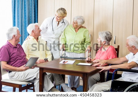 Seniors with wheelchair and walking aid in a retirement home - stock photo
