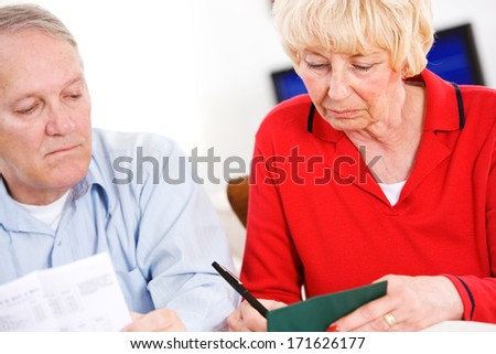 Seniors: Writing Checks For Monthly Bills - stock photo