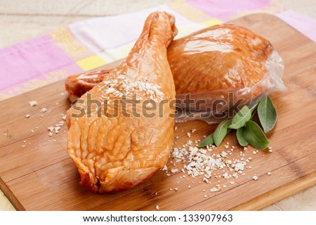 sensational smoked leg of chicken seasoned with coarse salt on a plain wooden plate - stock photo