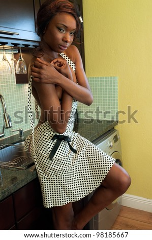 Sensual african american woman in a modern kitchen - stock photo