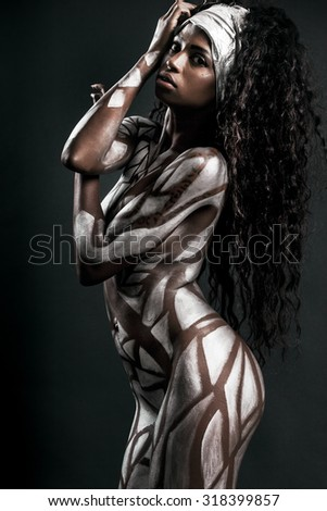 Sensual african model posing with body painted with white polygons - stock photo