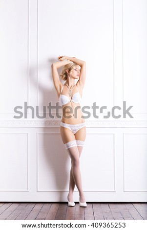 Sensual and beautiful young girl in a bridal lingerie over retro background - stock photo