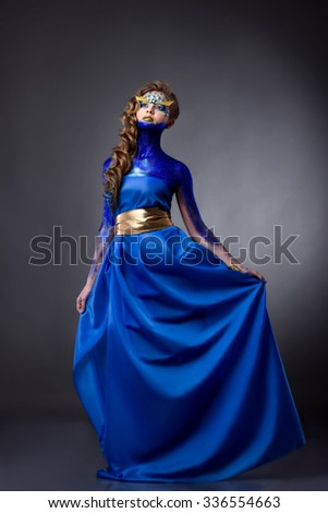 sensual attractive woman in blue glitter, rhinestones on face, royal blue dress,  golden belt, standing, grey background - stock photo