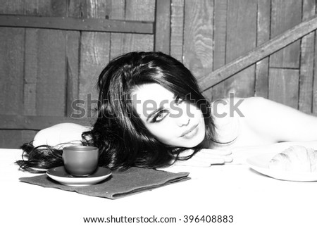 Sensual attractive woman with long brunette hair and bright makeup sitting behind table having breakfast of coffee and big burger on wooden background, horizontal picture - stock photo