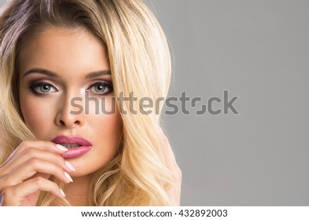 Sensual beautiful blonde woman posing. Girl with long curly hair and fashion makeup  - stock photo