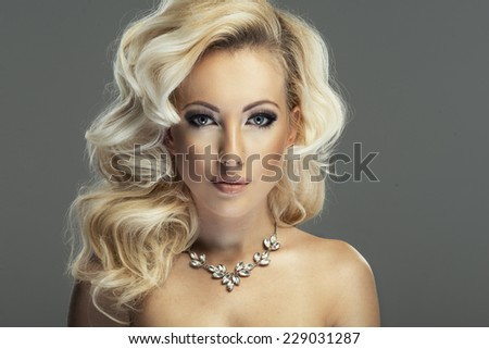 Sensual beautiful blonde woman posing in sensual lingerie. Girl with long curly hair.  - stock photo