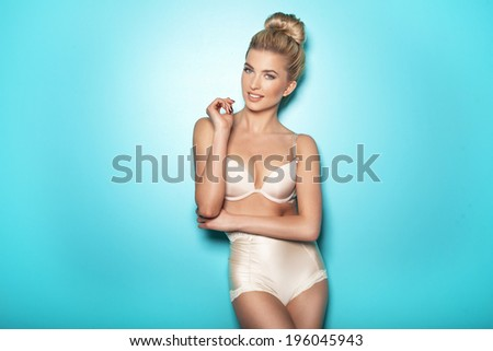 Sensual beautiful blonde woman posing in sexy lingerie, looking at camera. Smiling - stock photo