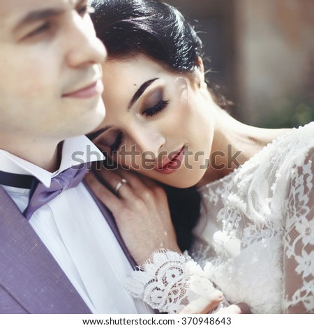 Sensual beautiful brunette bride leaning against valentine groom closeup - stock photo