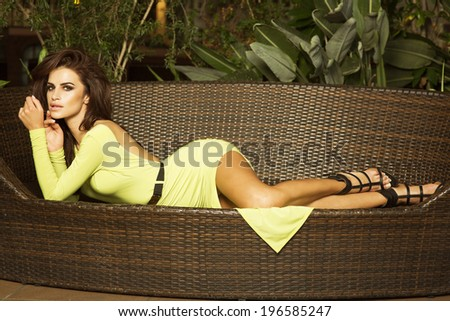 Sensual beautiful brunette woman posing in fashionable dress, lying, looking at camera. Summer photo. - stock photo