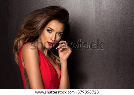 Sensual beautiful brunette woman posing in red dress. Girl with long curly hair.  - stock photo