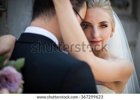 Sensual blonde bride hugging strong groom, face closeup - stock photo