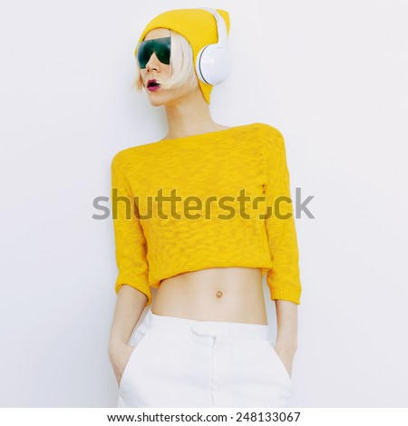 Sensual blonde DJ in bright clothes listening to Music - stock photo