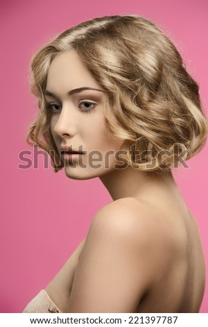 sensual blonde girl posing in beauty shoot with healthy short curly hair, natural make-up and naked shoulders  - stock photo