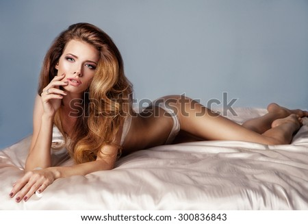 Sensual blonde woman posing in white sexy lingerie , looking at camera. Studio shot - stock photo