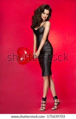Sensual brunette beauty posing with heart over red background, looking away. Studio shot. - stock photo