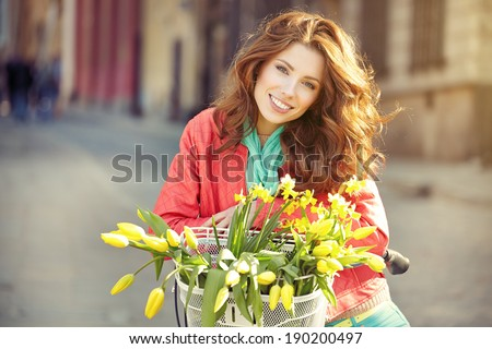 sensual brunette girl sitting on bicycle with some spring flowers in the basket  - stock photo