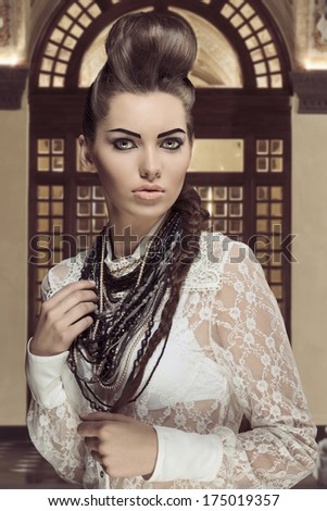 sensual brunette lady posing in fashion portrait with creative hair-style and cute make-up. Wearing sexy white lace shirt and a lot of necklaces  - stock photo