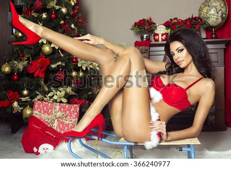 Sensual brunette woman in red lingerie posing, looking at camera. Perfect slim body. - stock photo