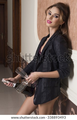 sensual brunette woman with lingerie and open jacket ready for the toast of the new year night taking bottle of champagne and glasses  - stock photo