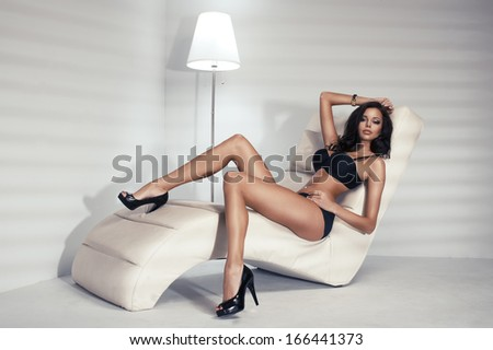 Sensual brunette woman with long curly hair lying in white bed, posing in sexy black lingerie, looking at camera. - stock photo
