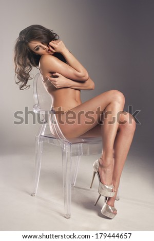 Sensual brunette woman with long curly hair sitting on chair, posing in sexy underwear  - stock photo