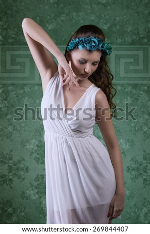 sensual brunette woman with long hair posing with spring style, coloured flowers on the head and sexy white dress  - stock photo