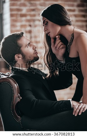 Sensual couple. Beautiful young woman in cocktail dress leaning to her boyfriend sitting in chair and holding his hand on her chin while looking at each other in loft interior - stock photo