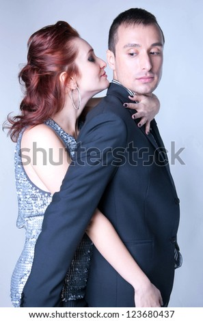 Sensual couple man and woman dressed in elegant clothes, standing close to each other, hugging in temptation, feeling desire, woman enjoying male scent, her eyes closed, man looking at woman. On gray - stock photo