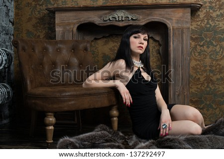 Sensual dark-haired woman in black dress sitting on fur in a vintage interior, horizontal shot - stock photo