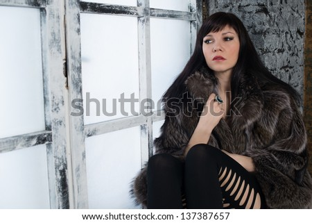Sensual dark-haired woman in fur coat sitting on a window sill and looking away, studio shot - stock photo