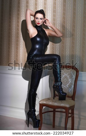 Sensual dominatrix in latex catsuit at vintage wall, step on chair - stock photo
